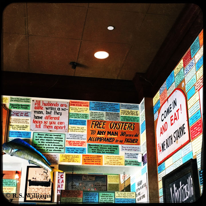 """Highly saturated color photo of the corner interior walls of Wintzell's Oyster House, in Montgomery, Alabama. Brightly colored, hand-lettered signs line the walls all the way up to the dark ceiling. The signs bear many various humorous old sayings, such as """"Come in and eat before we both starve"""" and """"Free oysters to any man 80 years old accompanied by his father."""""""